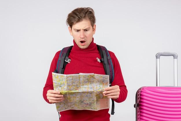 Vista frontal del turista masculino con mochila y mapa en la pared blanca