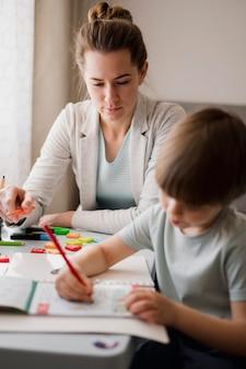 Vista frontal del tutor femenino enseñando a un niño en casa