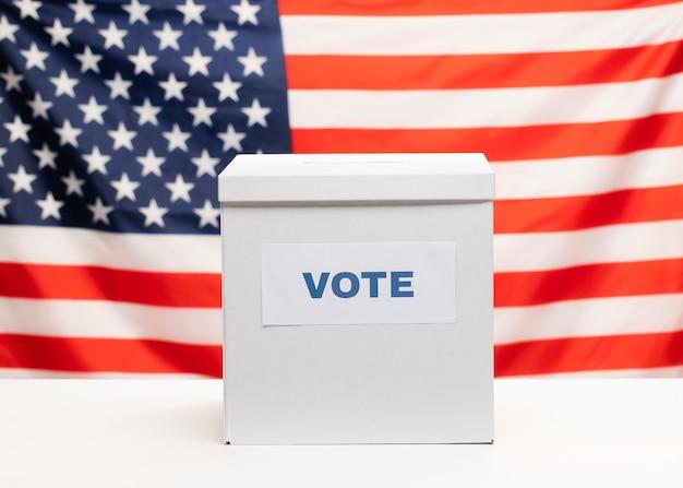 Vista frontal urna blanca y bandera americana
