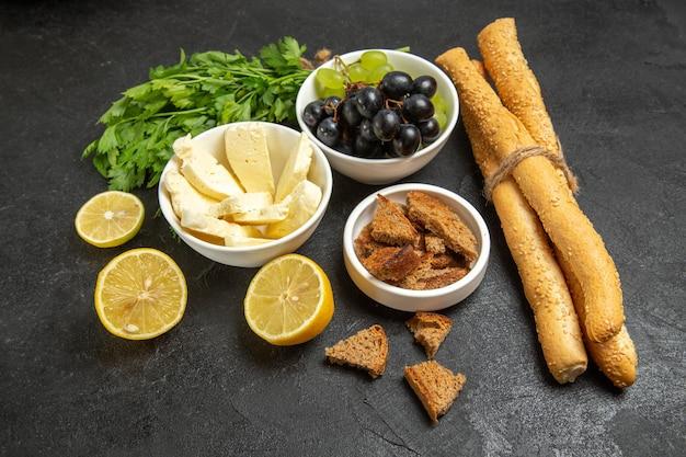 Vista frontal de uvas frescas con verduras de queso blanco y rodajas de limón sobre el fondo oscuro, comida, desayuno, plato, leche, fruta