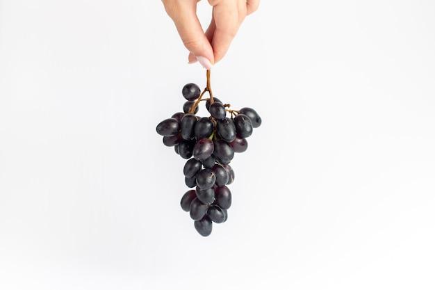 Vista frontal de las uvas jugosas frescas meloso ed negro sobre el fondo blanco.