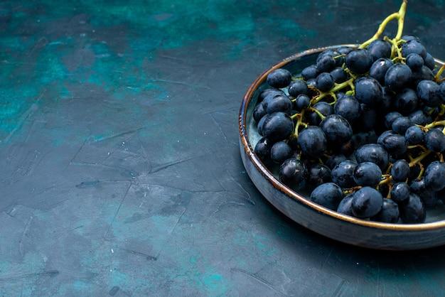 Vista frontal de uvas negras dentro de la bandeja en azul