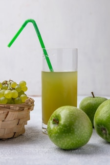 Vista frontal de uvas verdes en una canasta con pera manzanas verdes y jugo de manzana con una pajita verde en un vaso sobre un fondo blanco.