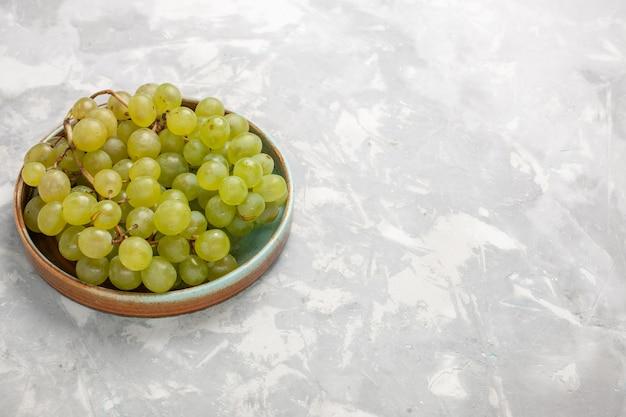 Vista frontal de uvas verdes frescas jugosas frutas dulces suaves en el escritorio blanco fruta fresca jugo suave vino