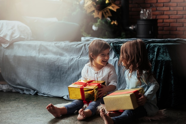 Vista frontal. vacaciones de navidad con regalos para estos dos niños que se sientan en el interior en la bonita habitación cerca de la cama