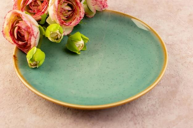 Una vista frontal vacía placa verde de vidrio en forma redonda junto con flores en rosa