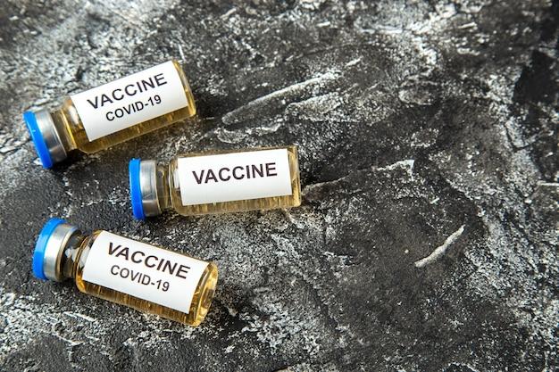 Vista frontal de la vacuna antivirus en pequeños frascos sobre fondo gris claro laboratorio de ciencias de la salud virus pandémico covid- hospital de aislamiento