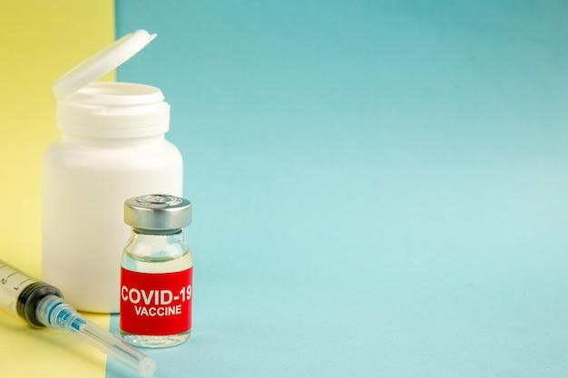 Vista frontal vacuna contra el coronavirus con inyección sobre fondo amarillo-azul virus del hospital covid- ciencia salud laboratorio de drogas pandemia color espacio libre