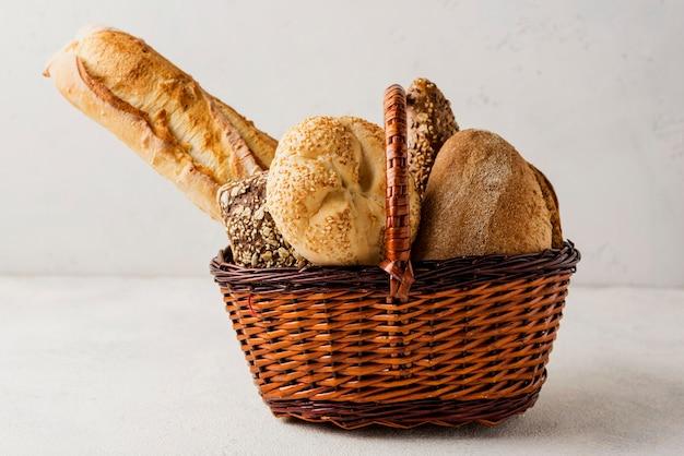 Vista frontal de varios pan blanco y grano entero en la cesta