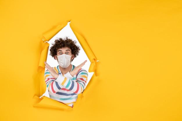Vista frontal del varón joven en máscara estéril en color amarillo salud foto covid- virus humano
