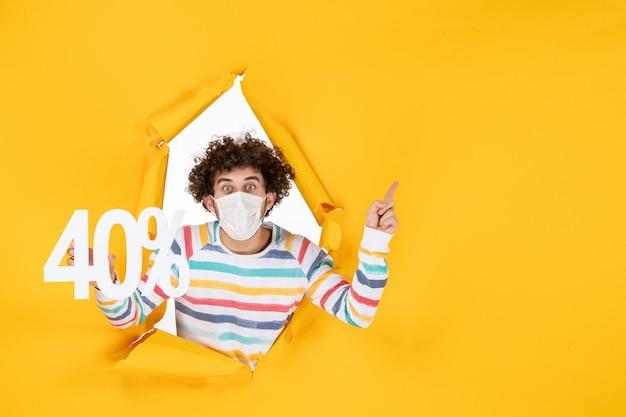Vista frontal del varón joven en la máscara que sostiene la escritura en el color amarillo de la pandemia del virus que compra la venta de la foto de la salud