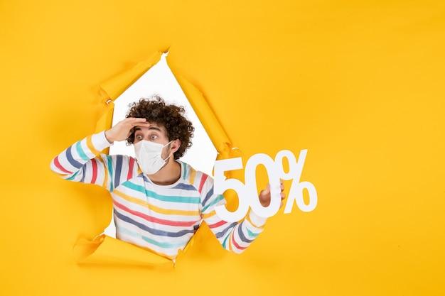 Vista frontal del varón joven en la máscara que sostiene la escritura en color amarillo de la venta de fotos del virus covid pandémico de salud