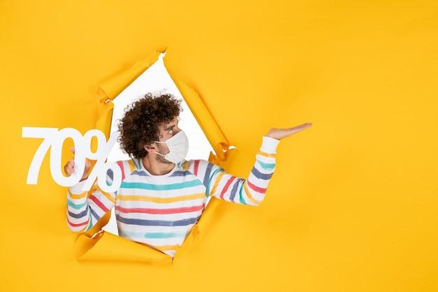 Vista frontal del varón joven en la máscara que sostiene la escritura en la venta amarilla colores comerciales covid- fotos virus pandemia de salud
