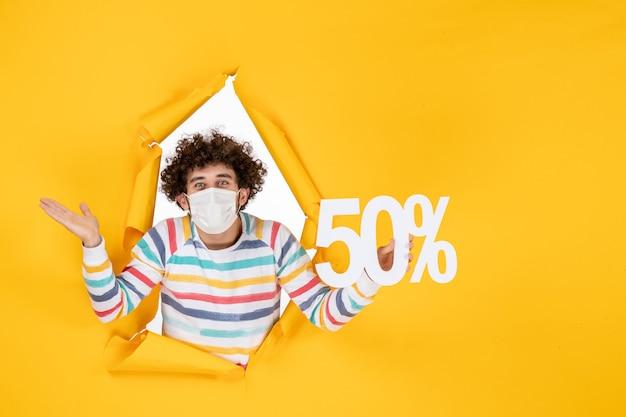 Vista frontal del varón joven en máscara sosteniendo la escritura en amarillo comercial salud pandemia covid- fotos venta color virus