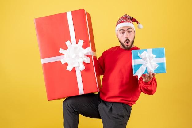 Vista frontal del varón joven con regalos de navidad sobre fondo amarillo