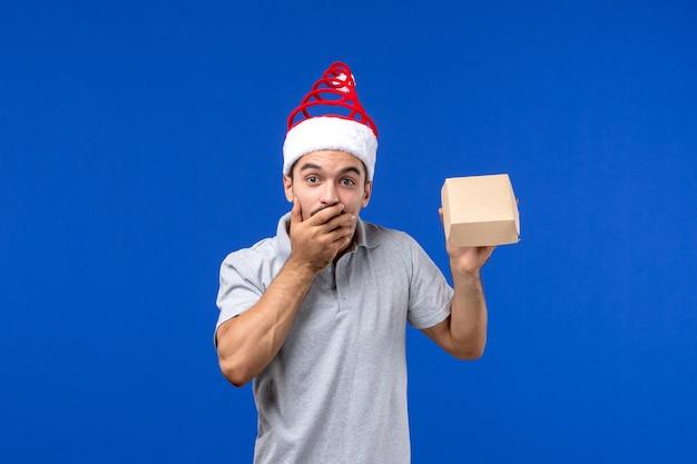 Vista frontal varón joven sosteniendo el paquete de alimentos en el trabajo de servicio de alimentos de pared azul