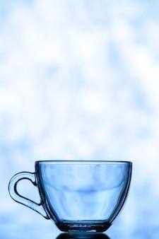 Vista frontal del vaso de agua azul sobre fondo azul espacio de copia borrosa