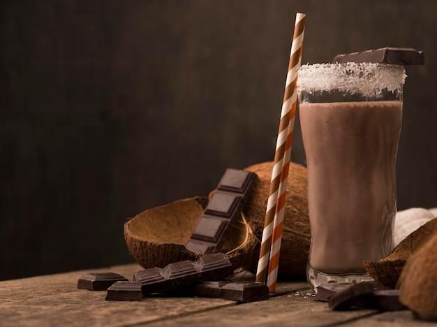 Vista frontal del vaso de batido en bandeja con coco y chocolate