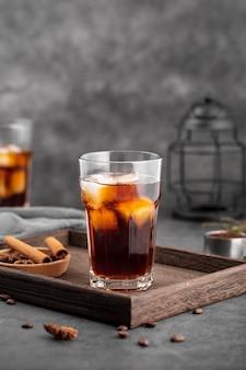 Vista frontal vaso de café helado sobre tabla de madera