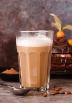 Vista frontal del vaso de chocolate con leche con cuchara y granos de café.