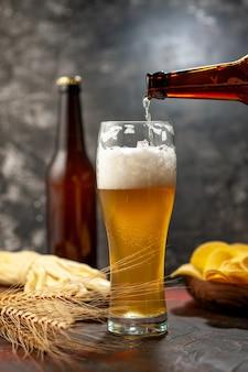 Vista frontal del vaso de oso con botella de cips y queso sobre vino ligero, bebida alcohólica, color de aperitivo