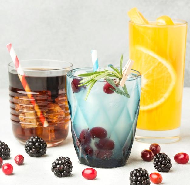 Vista frontal de vasos de cóctel de frutas con pajitas