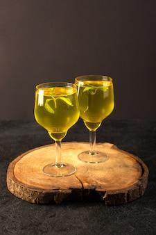 Una vista frontal vasos con jugo de jugo de limón dentro de vasos transparentes en el escritorio de madera marrón