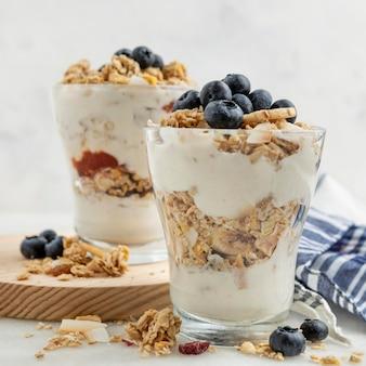 Vista frontal de vasos con yogur y cereales para el desayuno