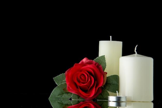 Vista frontal de velas blancas con flor roja sobre pared negra