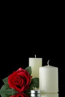 Vista frontal de velas blancas con flores rojas sobre pared negra