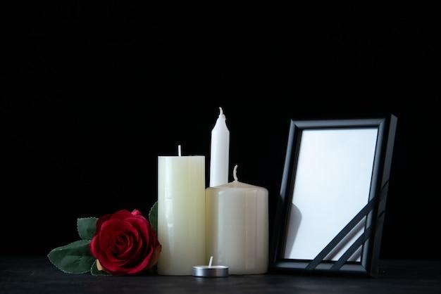 Vista frontal de velas blancas con rosa roja como memoria en la pared oscura