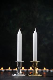 Vista frontal de velas encendidas como memoria de la superficie oscura caída