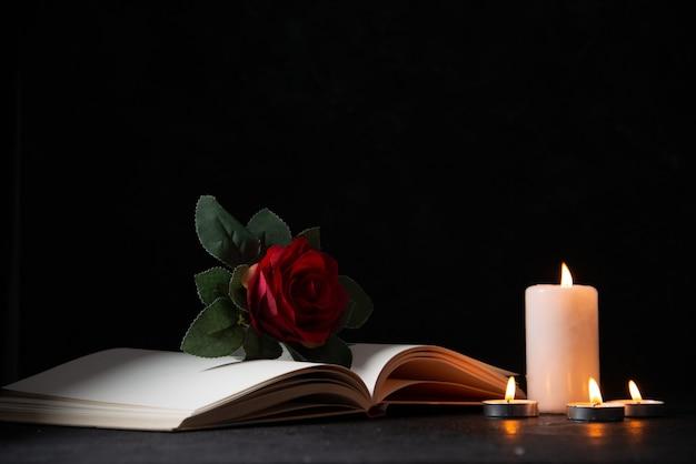 Vista frontal de velas encendidas con libro abierto y flor roja sobre superficie oscura
