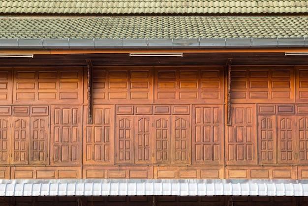 Vista frontal de la ventana de madera con tejas, fachada de casa de madera