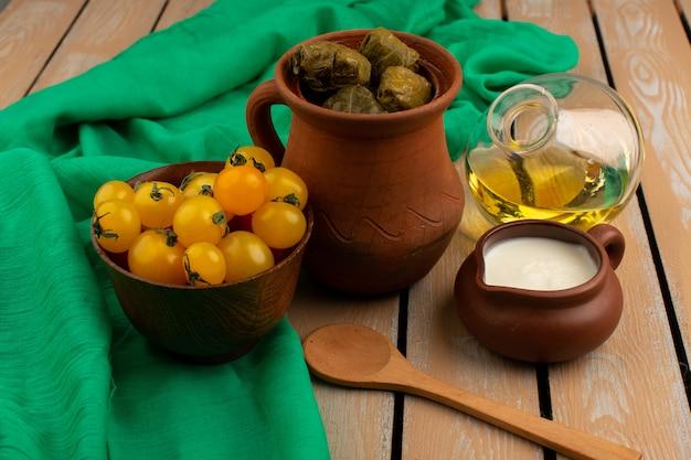 Vista frontal verde dolma harina de carne picada dentro de una olla marrón junto con tomates amarillos yogur y aceite de oliva en el marrón rústico