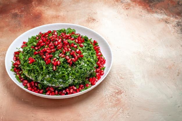 Vista frontal de verduras frescas con granadas peladas en la mesa de luz color de fruta verde