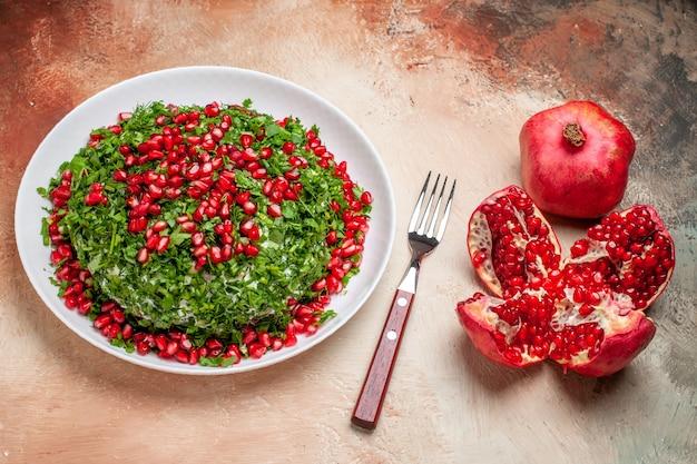 Vista frontal de verduras frescas con granadas peladas en una mesa de luz comida de fruta verde