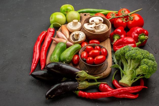 Vista frontal de verduras frescas maduras con setas en la mesa gris ensalada fresca de color maduro
