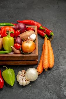 Vista frontal de verduras frescas con pimienta y ajo en el color de ensalada madura de mesa oscura