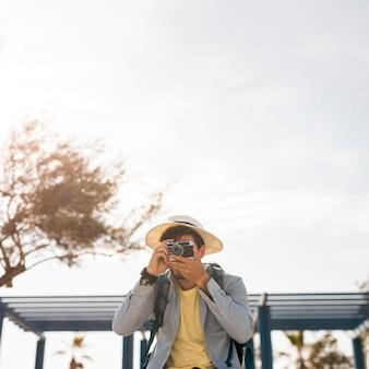 Vista frontal del viajero tomando fotos