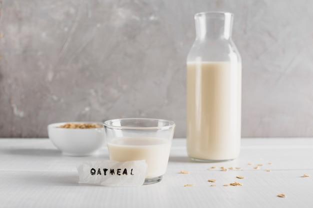 Vista frontal de vidrio y botella de leche con avena