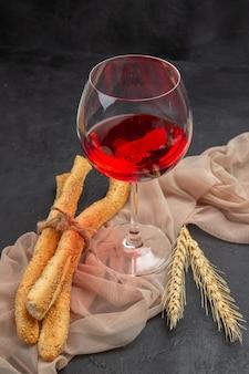 Vista frontal del vino tinto en una copa de cristal sobre una toalla sobre fondo negro