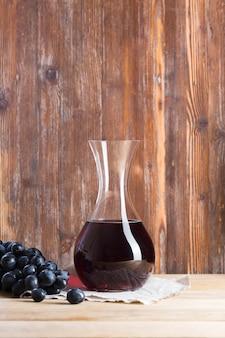 Vista frontal de vino tinto en jarra y uvas
