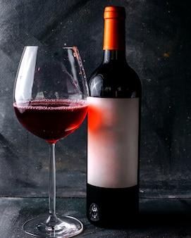 Vista frontal vino tinto junto con vidrio en el piso gris