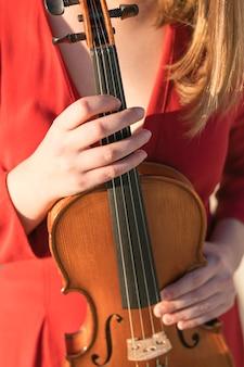 Vista frontal del violín sostenido por una mujer