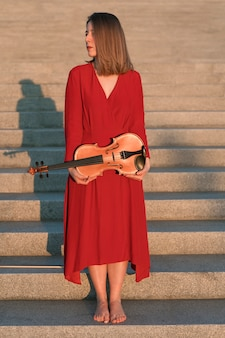 Vista frontal del violinista posando en pasos