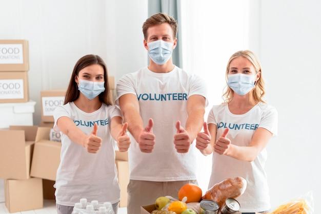 Vista frontal de voluntarios alegres para el día de la comida dando pulgar hacia arriba