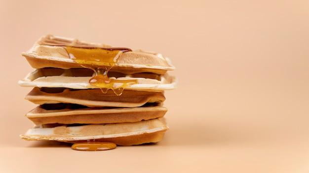 Vista frontal de waffle con goteo de miel y espacio de copia