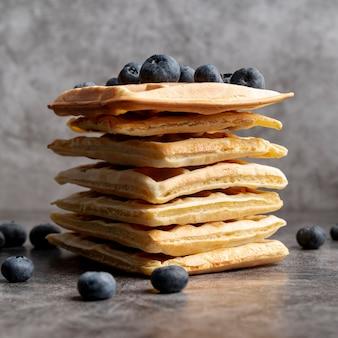 Vista frontal de waffles apilados con arándanos en la parte superior