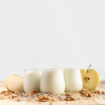 Vista frontal yogur natural en frascos con avena y manzana